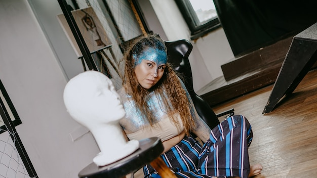 Kunstenaar in werkplaats. vrouw met blauwe glitters op haar gezicht. het concept van freaks en creatieve mensen. mensen zijn anders dan anderen. individualiteit