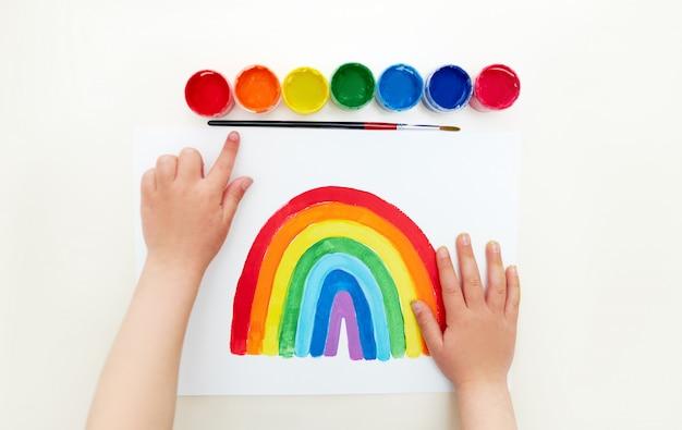 Kunstenaar kindje. jong geitje die de regenboog thuis schilderen tijdens quarantaine. verf instructie. kinderkaart voor verpleegsters