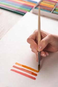 Kunstenaar kleurrijke strepen schilderen met penseel op wit papier