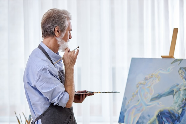 Kunstenaar man kijkt naar canvas zijn meesterwerk, sta denken, in contemplatie, geniet van tekenen, schilderen