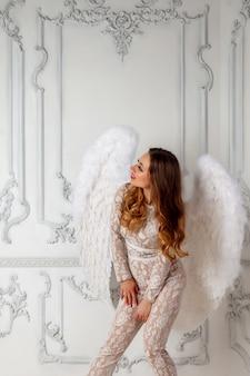 Kunstenaar meisje in een pak met vleugels op een vintage achtergrond. model kijkt naar de linkerbovenhoek. concept van een muziek- of modelposter. foto voor tijdschriftomslag, website met ruimte voor een opschrift of logo