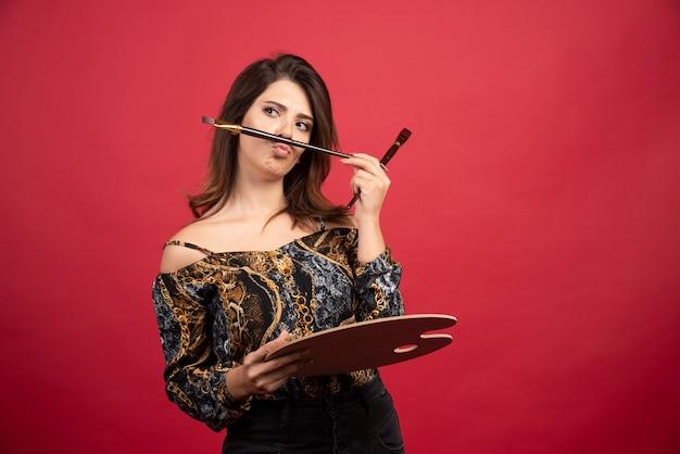 Kunstenaar meisje poseren met haar houten palet bord en penseel.