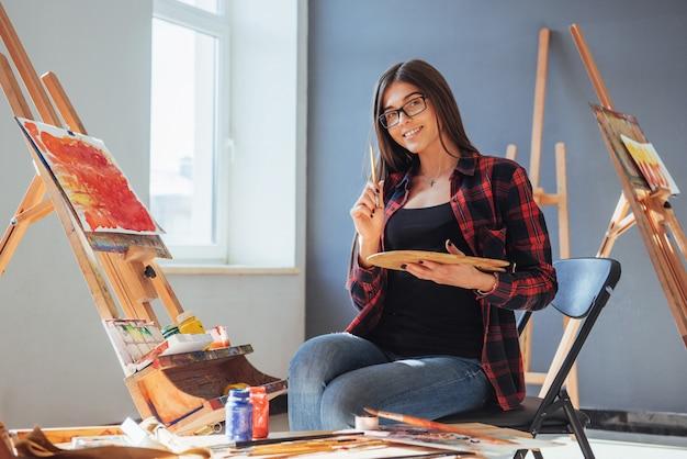Kunstenaar met een penseel in zijn hand en tekent een afbeelding op canvas