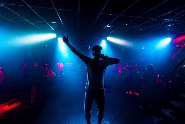 Kunstenaar met microfoon treedt op in een nachtclub