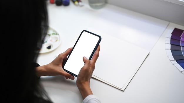 Kunstenaar of ontwerper die op creatieve werkruimte zit en mobiele telefoon gebruikt