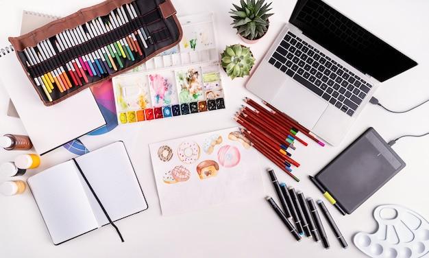 Kunstenaar of ontwerper werkruimte met laptop, tablet en tekengereedschap bovenaanzicht plat, overhead