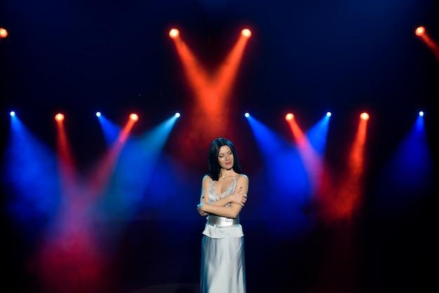 Kunstenaar poseren op het toneel in de club. heldere podiumverlichting