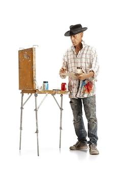 Kunstenaar schilder op het werk geïsoleerd op een witte studio achtergrond