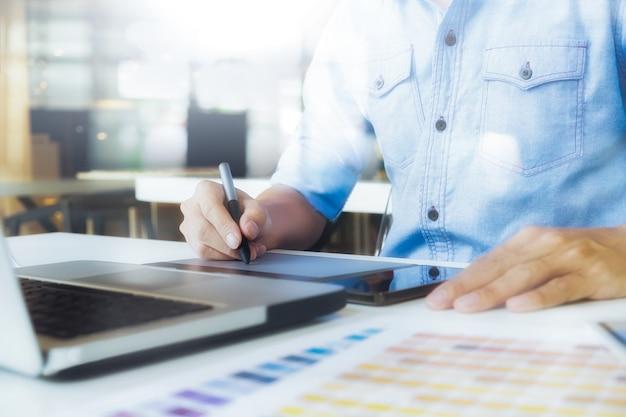 Kunstenaar tekening op grafische tablet met kleurstalen in kantoor. architectonische tekening met werkgereedschap en accessoires.