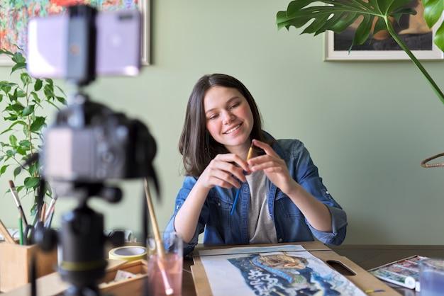 Kunstenaar, tienermeisje, tekent en registreert op videocamera voor zijn blog. verven, tekeningen op een thuistafel, camera op statief, tekenen vertellende blogger-vlogger. technologie, kunst, jeugd, onderwijsconcept