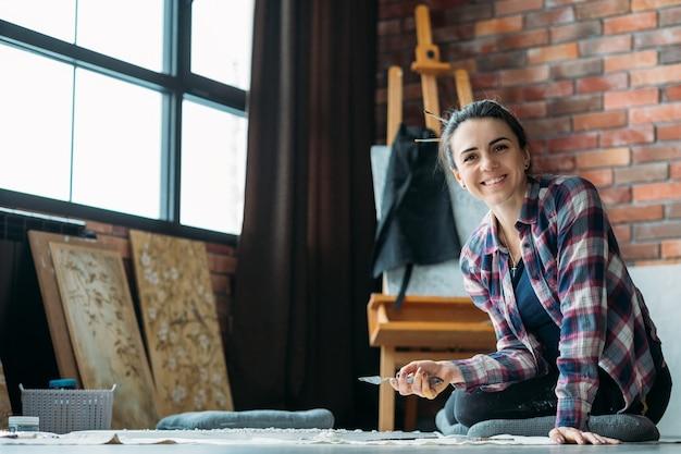 Kunstenaar verrukking. glimlachende vrouw met canvas en paletmes zittend op de vloer en camera kijken. kunstwerken en kunstbenodigdheden rond.
