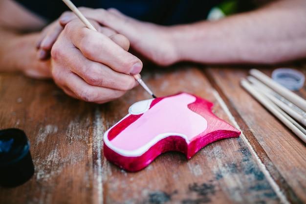 Kunstenaar versiert houten detail met roze verf