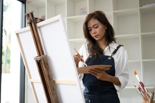 Kunstenaar vrouw schilderen met aquarellen in de werkplaats.