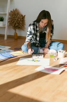 Kunstenaar vrouw schilderij op de vloer