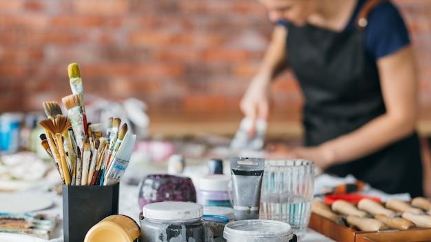 Kunstenaar werkplek. borstels, flessen en modelleertools. kunstwerk. vrouw in schort werken in studio. inspiratie.