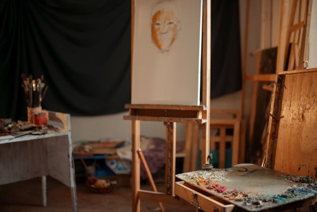 Kunstenaar workshop interieur, schildersatelier, niemand. schilderbenodigdheden. kleurenpalet, penselen en ezel, tekengereedschappen en apparatuur