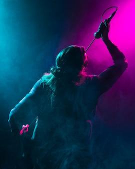 Kunstenaar zingt op de microfoon van achter schot