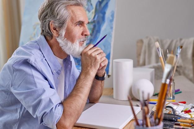 Kunstenaar zit achter tafel en denkt wat te tekenen, schilderen. oudere mannen gebruiken potlood voor tekeningen