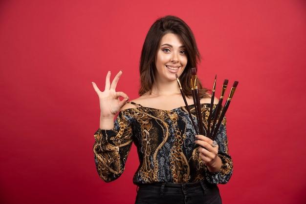 Kunstenaarmeisje demonstreert haar set nieuwe merkborstels en ziet er tevreden uit.