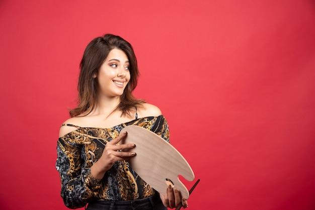 Kunstenaarmeisje toont haar palet aan de curator of meester ter beoordeling.