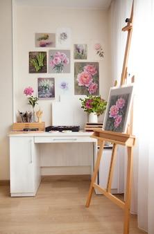 Kunstenaars thuiswerkplek wit licht houten tafel om te schilderen met ezel en prachtige kunstwerken met bloemen aan de muur en tekengereedschappen. creativiteit en hobby-concept