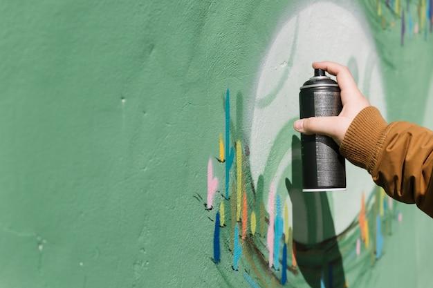 Kunstenaarshand die op graffitimuur bespuiten met aërosolnevel