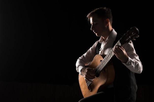 Kunstenaarsmens die op stadium de ruimte van het gitaarexemplaar spelen