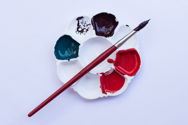 Kunstenaarspalet met diverse kleurenverven op witte achtergrond