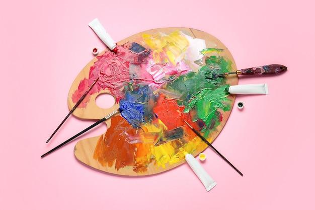 Kunstenaarspalet met verven op gekleurde achtergrond
