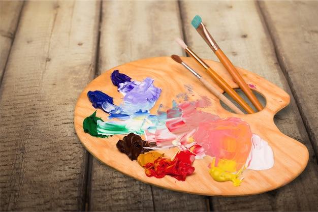 Kunstenaarspenselen en verfpalet op houten achtergrond