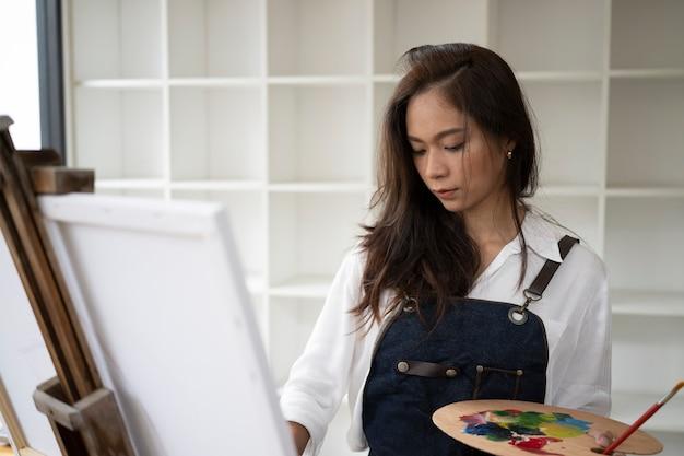 Kunstenaarsvrouw die in schort een beeld schilderen bij kunstworkshop.