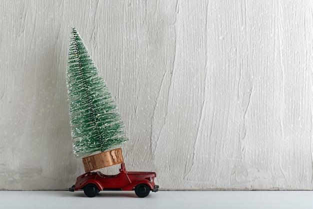 Kunstkerstboom staat op kleine speelgoedauto. levering van bomen. auto als cadeau.