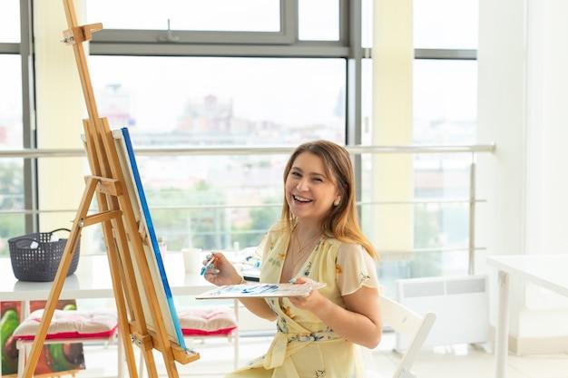 Kunstles en tekenconcept - vrouw kunstenaar bezig met schilderen