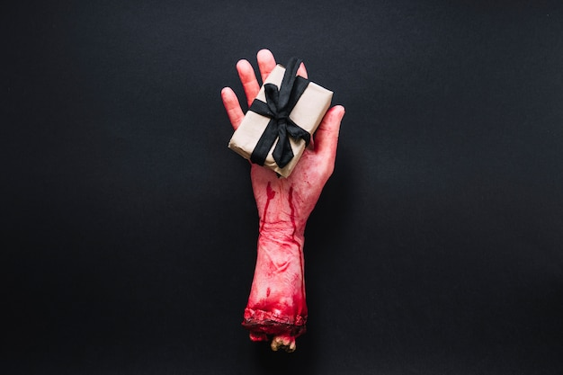 Kunstmatig afgehakte hand met verpakt cadeau