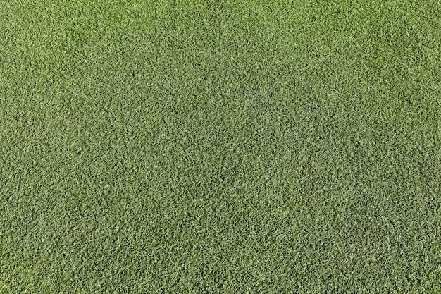 Kunstmatig groen gras, de oppervlaktetextuur van het voetbalveld, bovenaanzicht