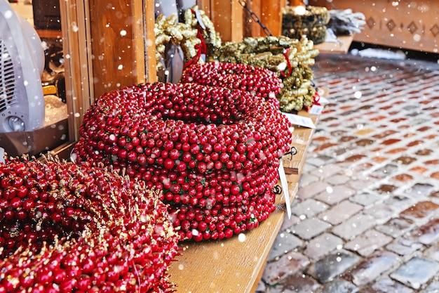 Kunstmatige decoratieve krans met rode bessen op teller tijdens traditionele kerstmarkt in de straat van de stad tallinn