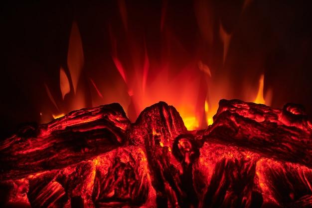 Kunstmatige elektrische open haard met rode, oranje en gele vlam, brandende houtblokken.