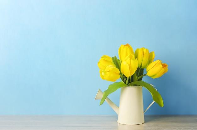 Kunstmatige gele tulp bloemen op gieter