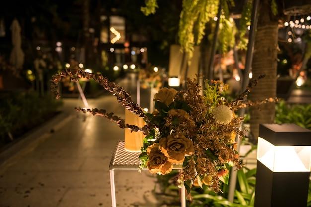 Kunstmatige gouden bloemen en kaarsdecoratie in de buitenhuwelijksceremonie van de nacht in de tuin van het resort.