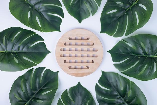 Kunstmatige groene bladeren en houten plaat wit oppervlak.