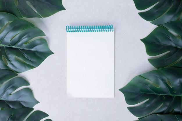 Kunstmatige groene bladeren met notitieboekje op wit.