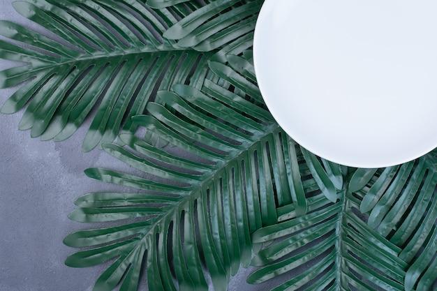 Kunstmatige groene bladeren rond witte plaat op blauw.