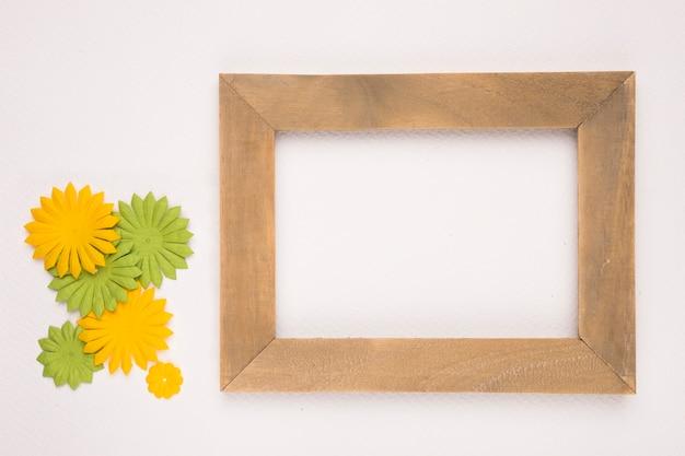 Kunstmatige groene en gele bloemen dichtbij het houten lege kader op witte achtergrond