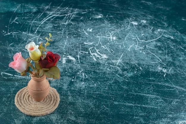 Kunstmatige kleurrijke rozen in een kleivaas op een onderzetter, op de blauwe achtergrond.