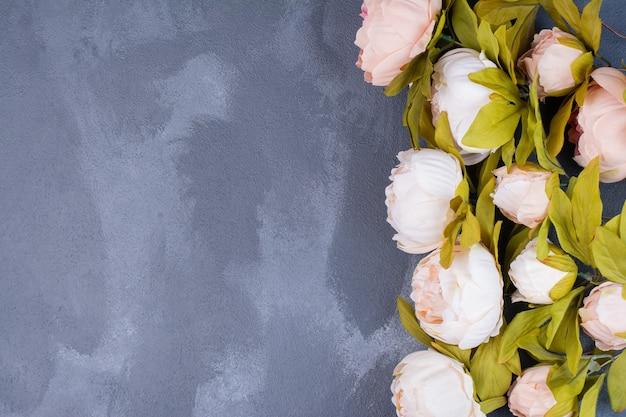 Kunstmatige mooie bloemen op blauw.