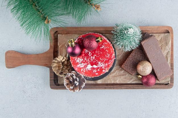 Kunstmatige pijnboomtak naast een dienblad met geassorteerde desserts op marmeren achtergrond.