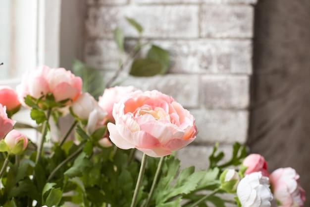 Kunstmatige roze bloemen op witte bakstenen muur
