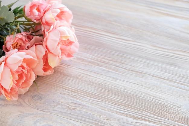 Kunstmatige roze pioenrozen bloemen op een houten bord. kopieer ruimte