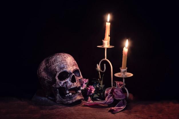 Kunstmatige schedel en kandelaar op houten laag op zwarte achtergrond