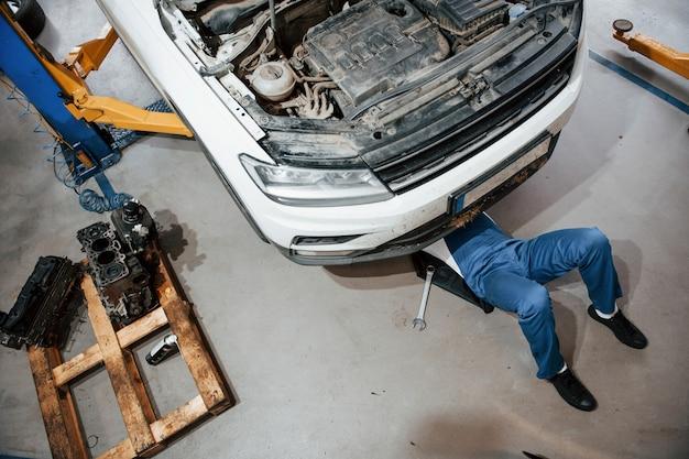 Kunstmatige verlichting. werknemer in het blauw gekleurde uniform werkt in de autosalon